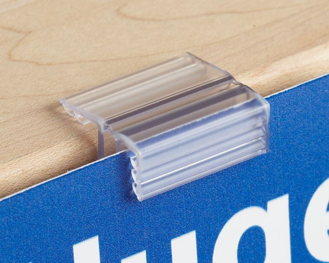 Merchandising sign gripper attaches to wood and glass tables for displaying price tags.