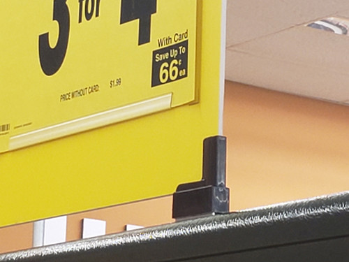 Cost effective magnetic base boot for displaying signs on Lozier shelving and similar metal shelves.