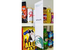 grocery store asile shelf plastic sign holder on beverage shelf with sign