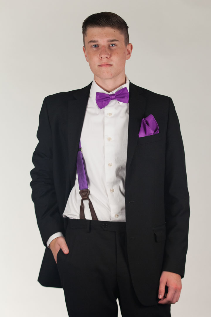 Model wearing pocket square, suspenders and bow tie