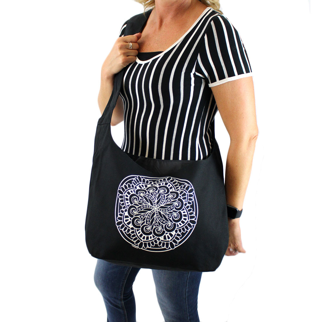 Black canvas sling bag with white Mandala on front of bag shown on front side of person.