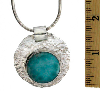 Handmade Larimar pendant with hammered detail seen with ruler.