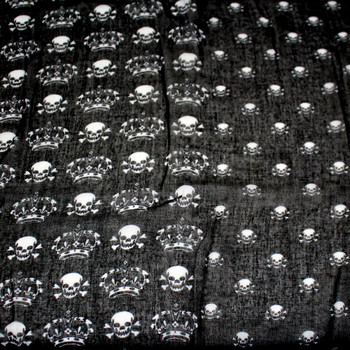 Black scarf with skulls and crossbones and crowns close up picture.