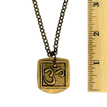 OM necklace with ruler showing the size of pendant.