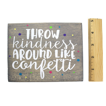 Front side with ruller of small wooden sign Throw Kindness Around Like Confetti.