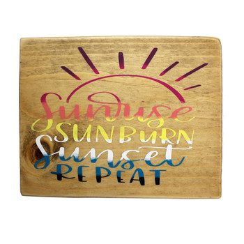Front side of small wooden sign Sunrise Sunburn Sunset Repeat.