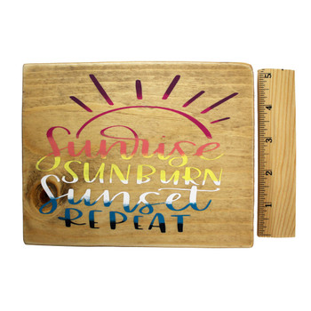 Front side with ruler of small wooden sign Sunrise Sunburn Sunset Repeat.