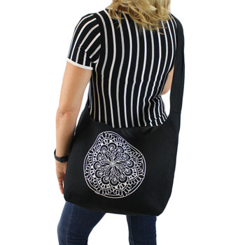 Black canvas sling bag with white Mandala on front of bag shown on back of person.