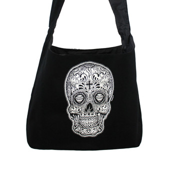 Close up picture of black and white Day of the Dead skull on black canvas sling bag.