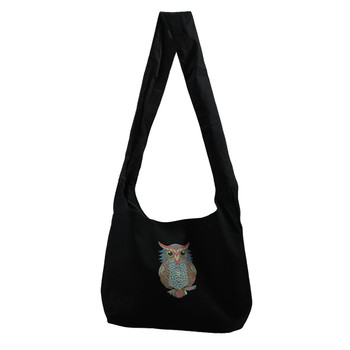 Black canvas sling bag with a small colorful owl on front of bag.