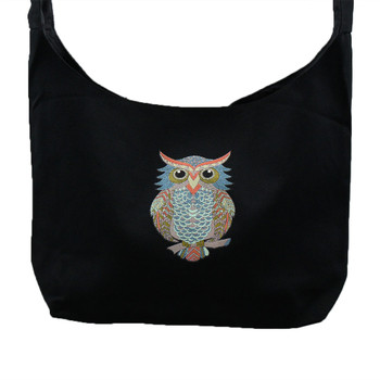 Close up of black canvas sling bag with a small colorful owl on front of bag.