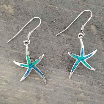 Starfish sterling silver earrings on wood.