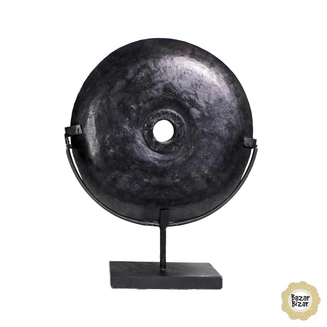 Een  grote, zwarte, ronde, gepolierde riviersteen op een op maat gemaakte standaard als decoratiestuk.