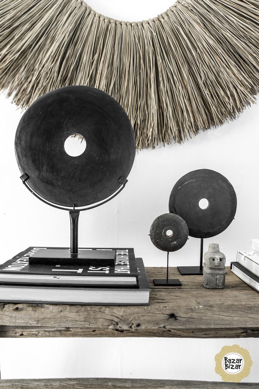 Een zwarte, ronde, gepolierde riviersteen op een op maat gemaakte standaard als decoratiestuk, in een interieur.