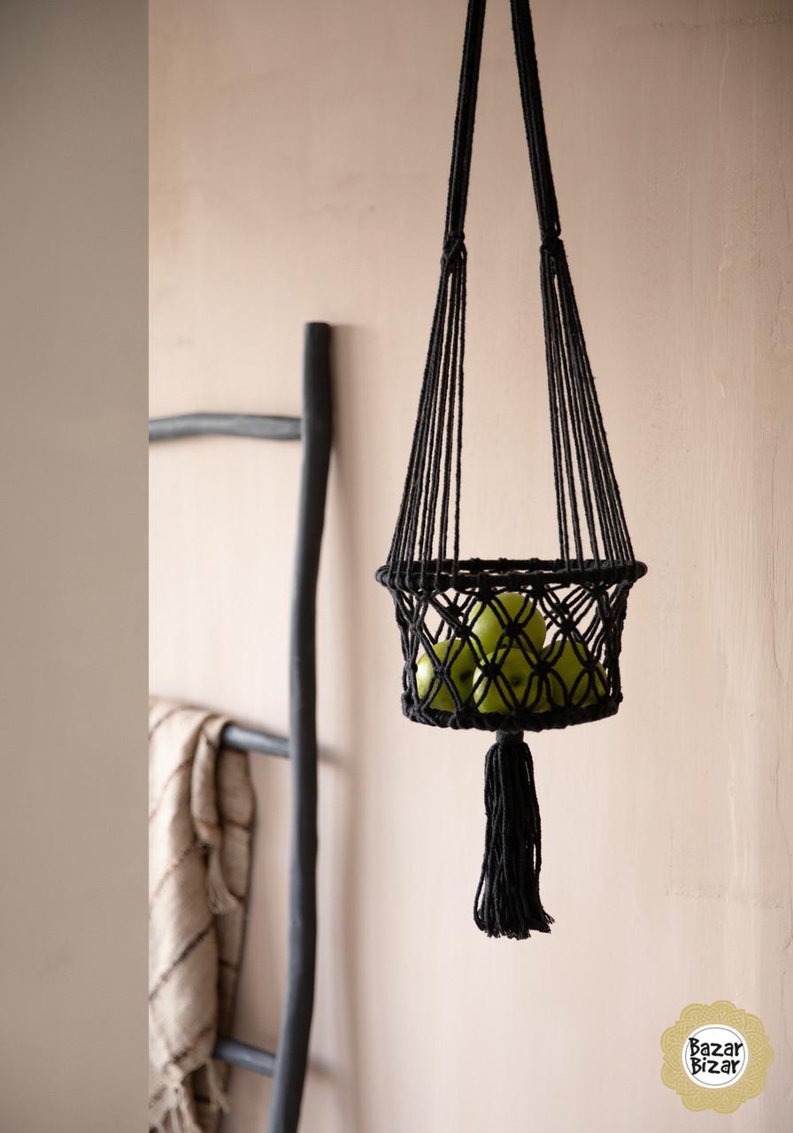 Een zwarte macrame hangmand met onderaan een grote tassel in de zwarte kleur in een interieur.