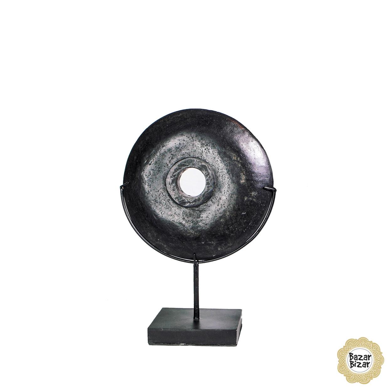 Een zwarte, ronde, gepolierde riviersteen op een op maat gemaakte standaard als decoratiestuk.