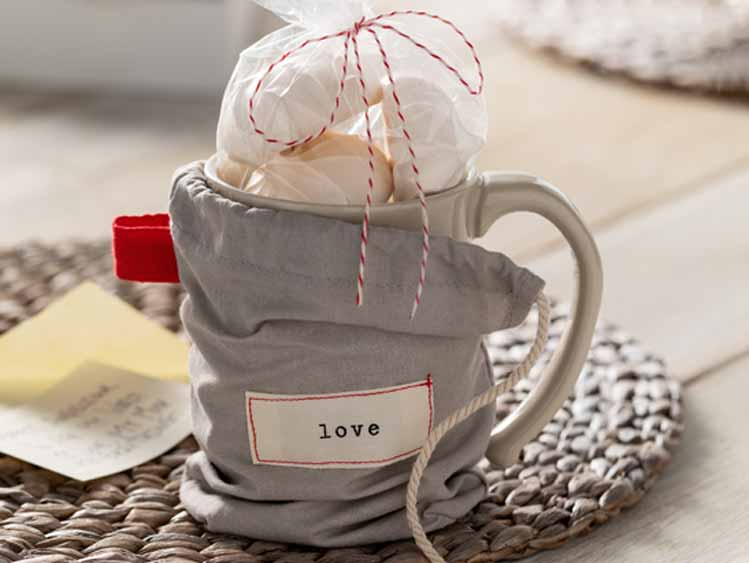 ceramic cup gift that packaged in a small gray pouch placed on living room table.