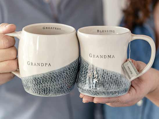 Couple holding mugs together that fit together that say Grandma and Grandpa