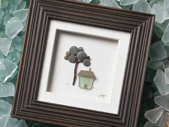 Framed artwork of a house made by tiny gray pebbles and blue-green sea glass