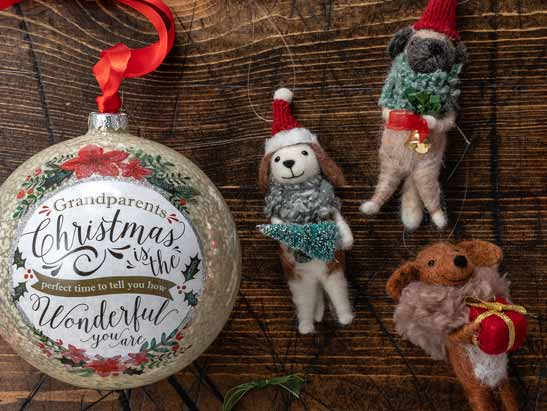 Christmas ornaments lying on a wood table. Large bulb with the words Grandparents Christmas is the perfect time to tell you how wonderful you are. Fuzzy dogs holding bells and a christmas tree.