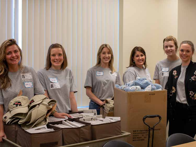Group of DEMDACO employees volunteering - women standing in front of boxes of product