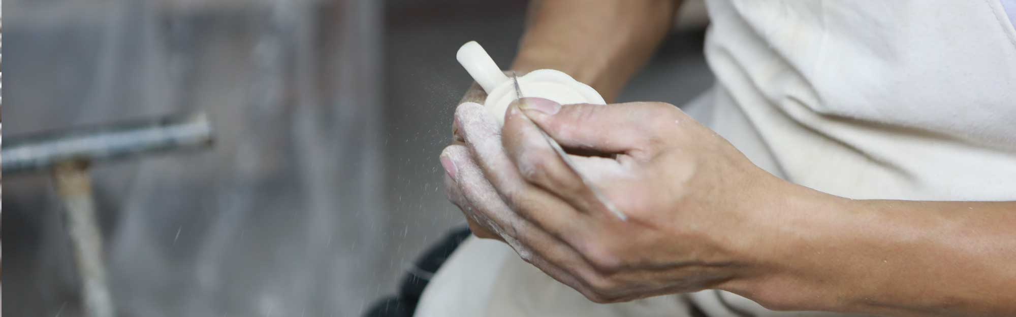 Hand covered in dust carving unfinished ceramic dish