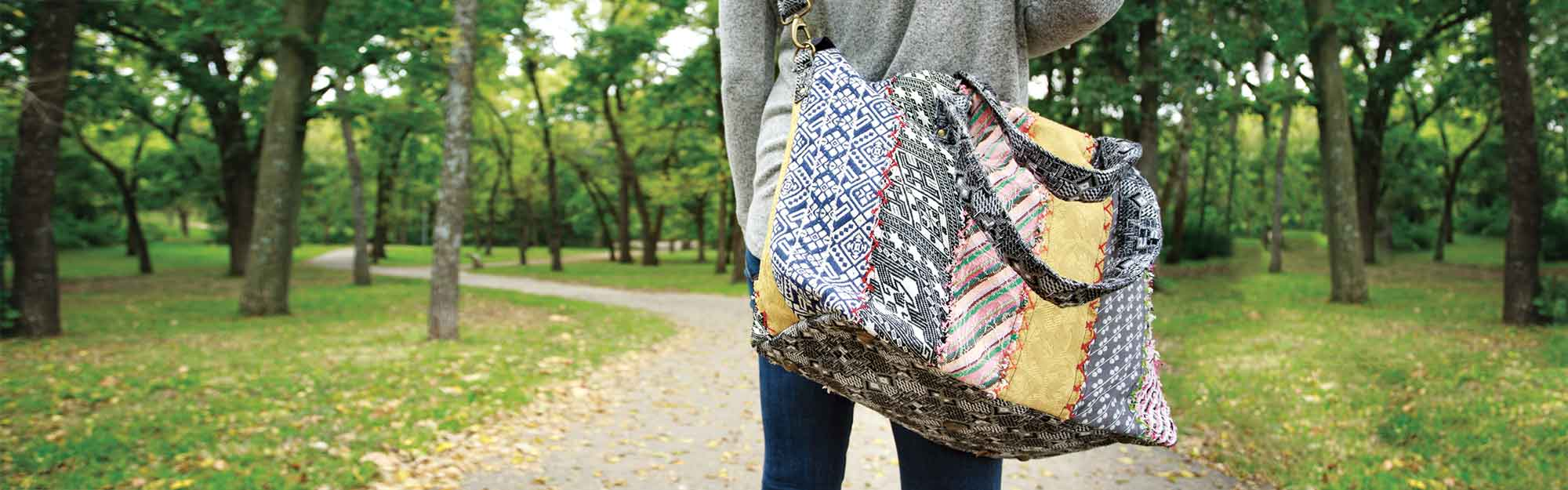 Woman walking down a wooded path carrying a colorful hand-stitched bag over her shoulder
