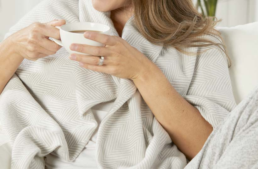 Woman wrapped in soft, cream shawl sitting on a couch drinking from a mug