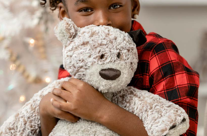 Child hugging a soft teddy bear in front of a Christmas tree
