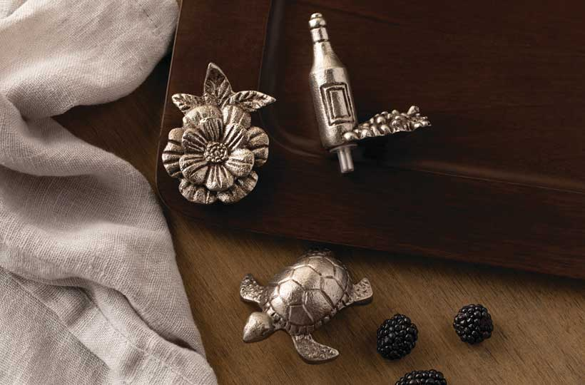 Silver metal flower, turtle, and wine bottle decorations on a dark wooden serving platter