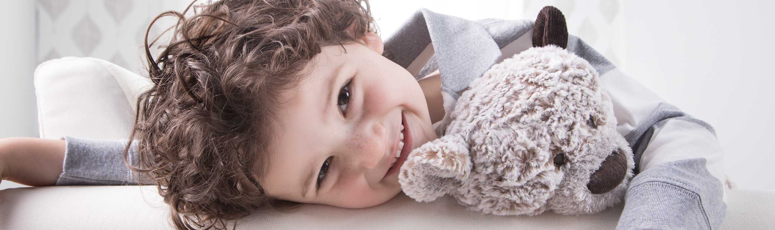 Smiling boy hanging over couch with soft brown teddy bear