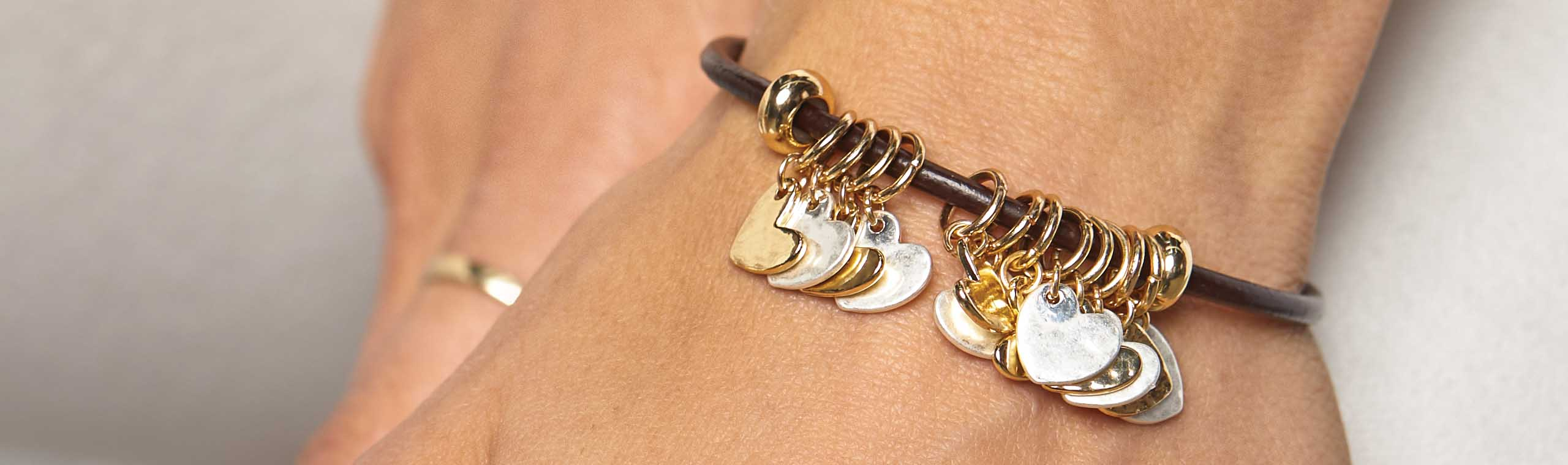 Woman wearing gold bracelet with gold and silver heart charms