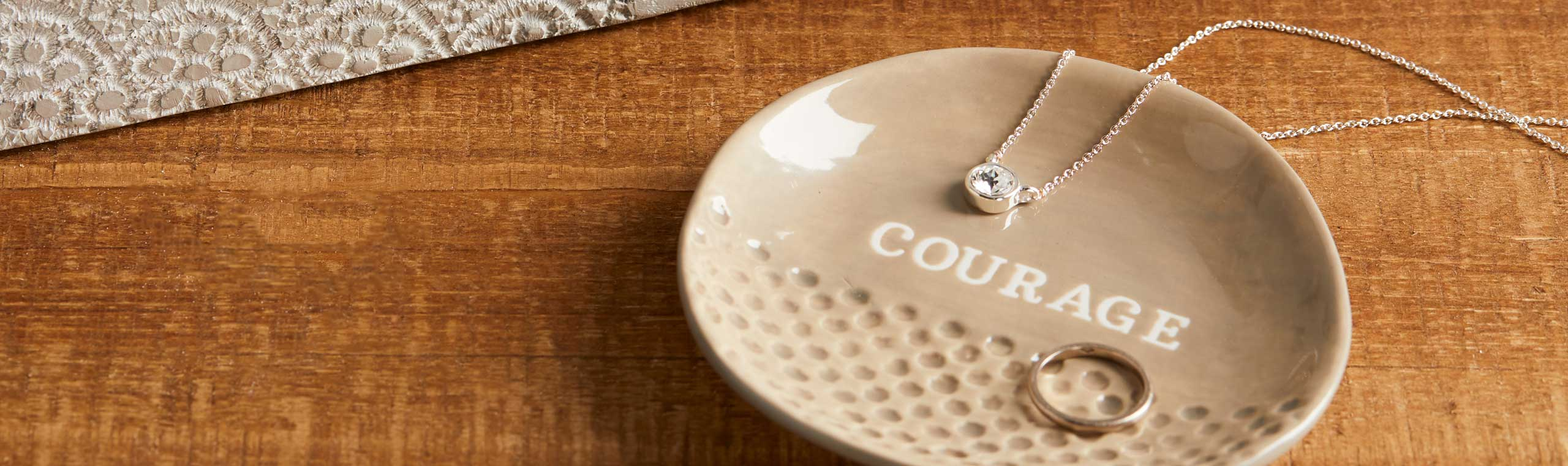 Tan ceramic dish embossed with the word courage holding a ring and necklace