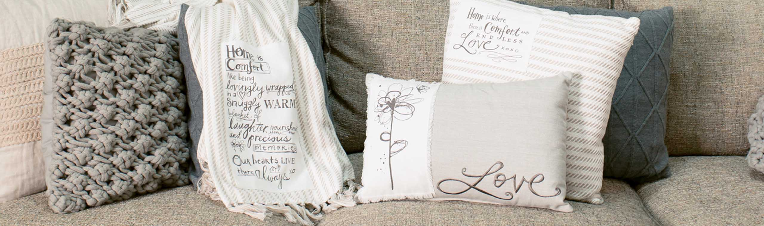 Soft white and gray pillows and blanket draped on living room couch