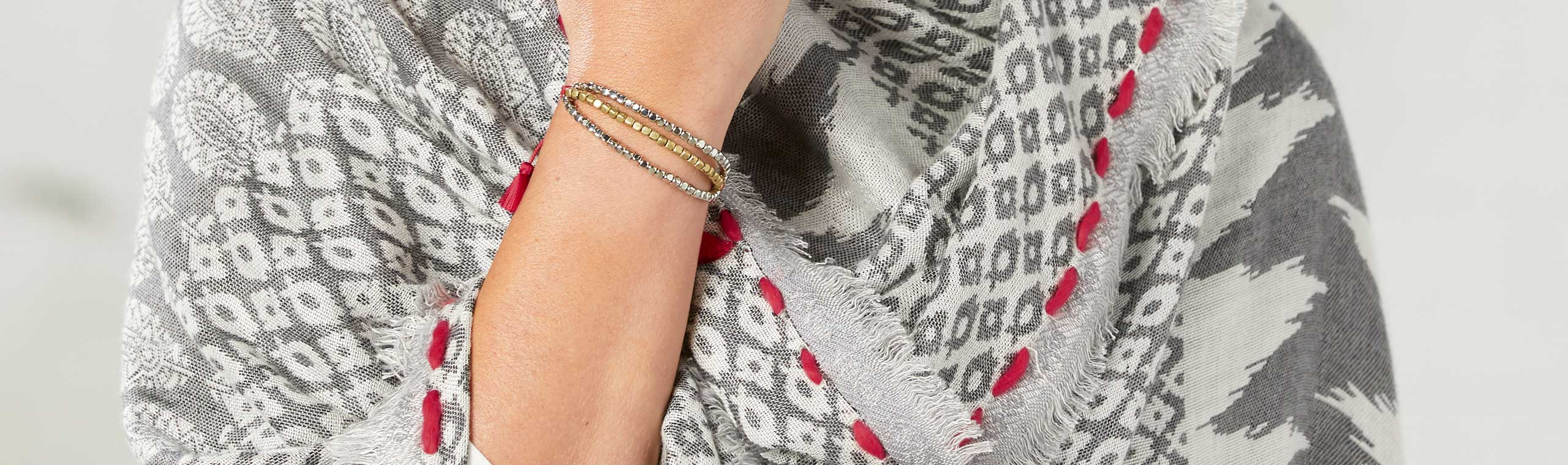 Woman wearing gray wrap accented with bright red threads and gold and silver beaded bracelet with bright red threads