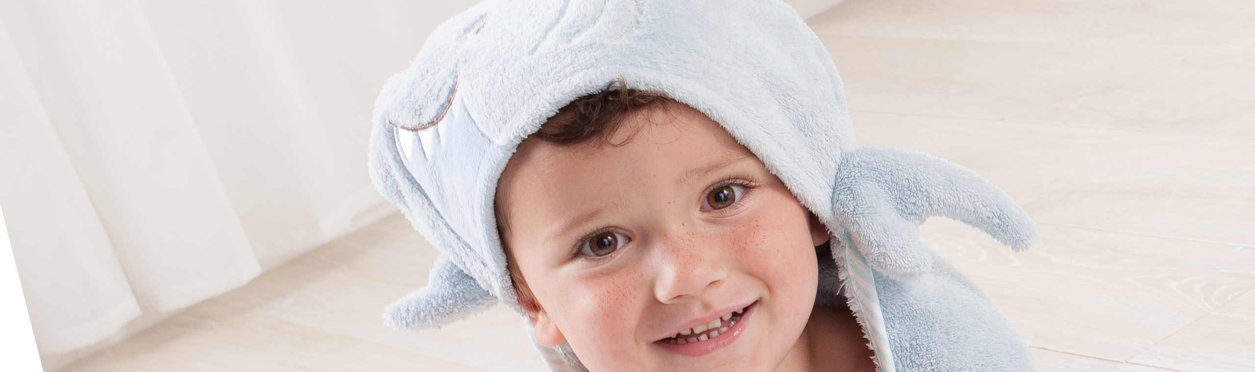 Boy wearing blue shark hooded towel on his head