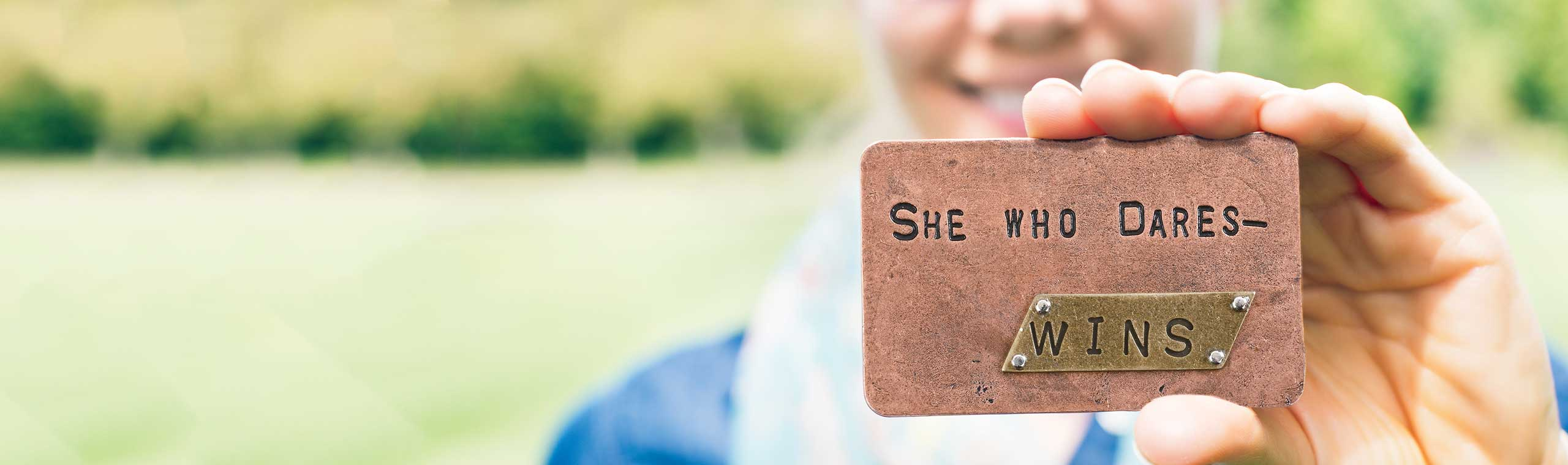 Woman holding a metal card with the words She Who Dares - Wins