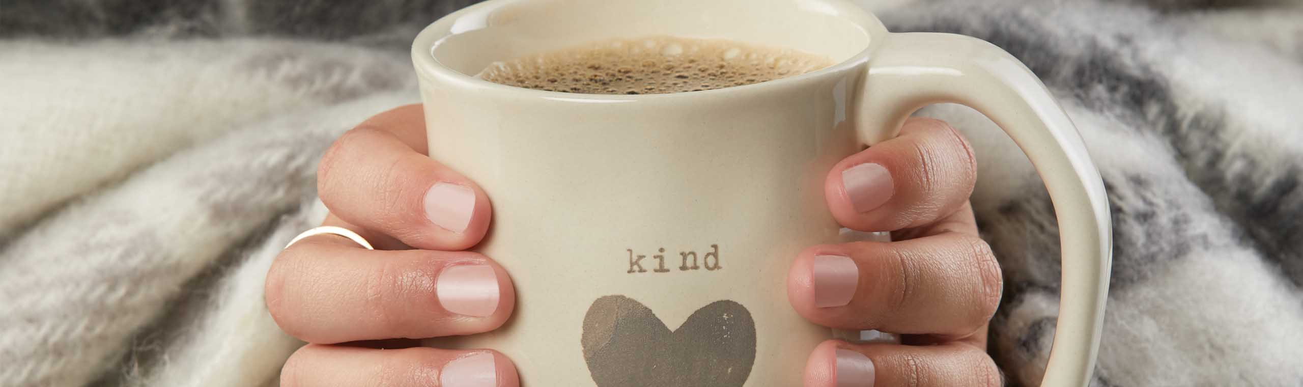 Hands around warm mug with heart decoration