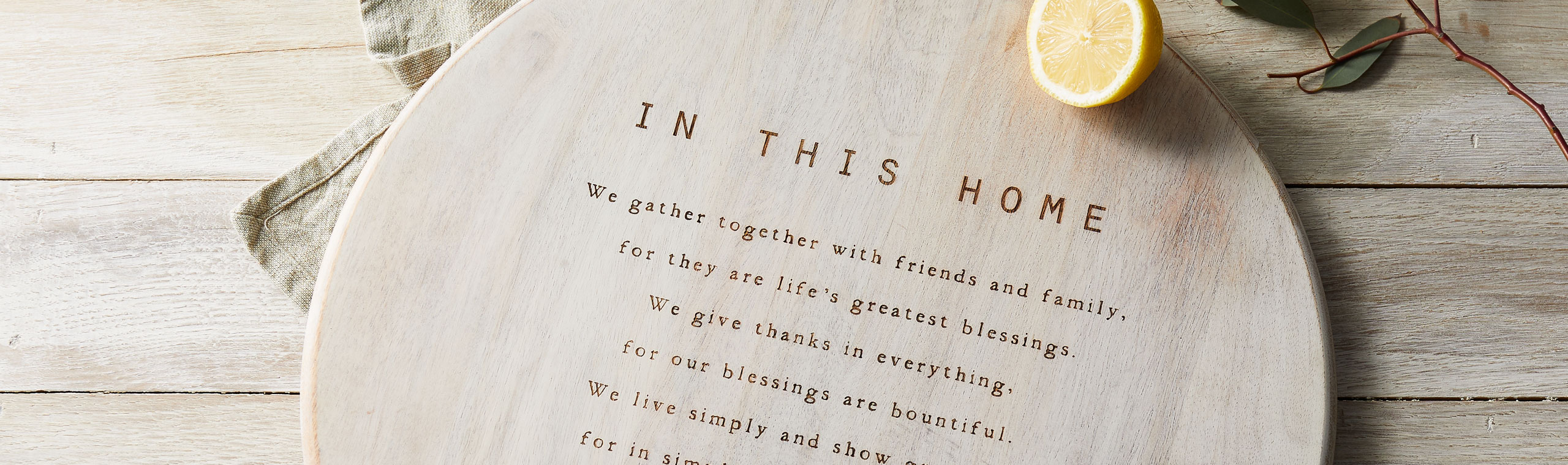 In This Home message engraved on the face of a round light wood platter on wooden table