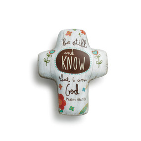 White cross figurine with 'be still and know that I am God' printed in brown around flower print
