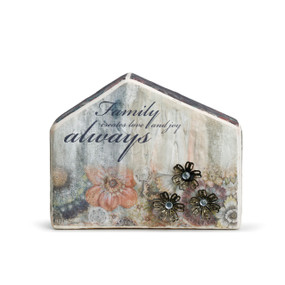 Front view of house. Text is grayish navy, various flowers in different colors printed on house, and three metal flower decals in lower right corner