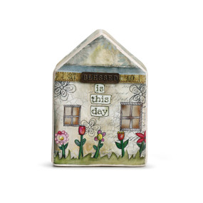 House figurine with 'blessed is this day' carved in above red tulips
