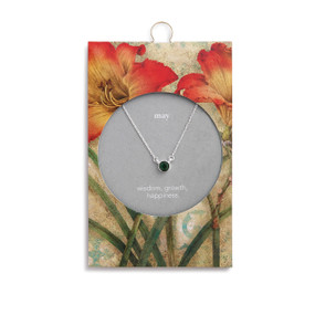 Silver chain necklace holds an emerald pendant. Packaging has yellow and red lilies