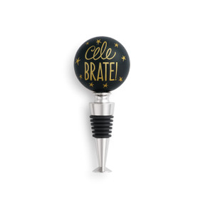 Bottle stopper has round, black top with gold colored dots and lettering. Bottom is metallic with black rubber.