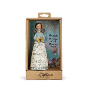 Angel with brown hair and wings wears a dress with a blue top and a white skirt with blue decal at bottom. Gray text and flowers are engraved on skirt. Yellow flower is in angel's hair as she holds a yellow butterfly. Angel is in brown gift packaging