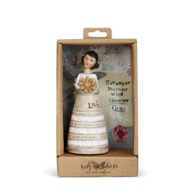 Angel figurine with brown hair and wings wears a dress with white top and sand&white striped skirt. Brown engraved lettering on skirt. Angel holds a yellow flower. Angel is in brown gift packaging