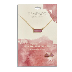 Gold necklace holds a rectangular pendant with a pink stone. Gold, triangular stud earrings have pink stones. Both necklace and earrings are on a white message card with pink accents