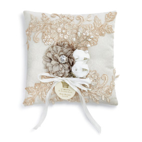 White pillow with gold flower crystal design, tan flower in middle under bow with A Gilded Life tag in gold letters