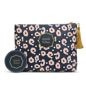 Black/pink printed purse with 'good vibes' in gold/black round banner next to round black token with 'good vibes' in yellow