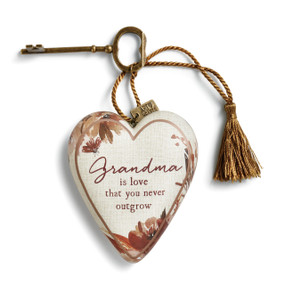 Small white heart with red flower border and 'grandma is love that you never outgrow' in the center - gold key and tassle attatched